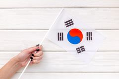 Independence Day of South Korea concept with flag in hand on white wooden background top view.  royalty free stock photos