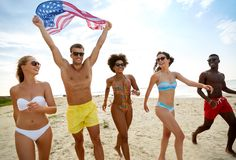 Happy friends with american flag on summer beach. Independence day, summer holidays and people concept - group of happy friends with american flag on beach stock photo