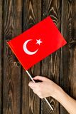 Independence Day of Turkey concept with flag in hand on wooden background top view.  royalty free stock images