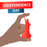 Independence Day United States. The fourth of July. The concept of the power of patriotism. Hand holding a chess piece. Statue of liberty- queen on white Royalty Free Stock Image