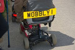 Independence with disability. Disabled scooter. Wobbly 1. A disability scooter ridden by a senior citizen with a sense of humor. With the help of the electric stock images