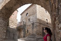 Independence flag, estelada, behind an arch made of stone in Per. Woman in an arch made of stone in Peratallada, Spain Royalty Free Stock Photography