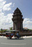 Independence Monument Phnom Penh. A tuk-tuk driver rides around the Independence Monument in Phnom Penh,  which was erected in 1958 for Cambodia's freedom from Stock Image