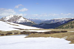 Independence pass vista. Alpine tundra partially covered by snow with snow capped peaks receding into background under partially cloudy blue skies stock photos