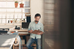 Independent designer businessman checking orders on his clipboar Royalty Free Stock Images