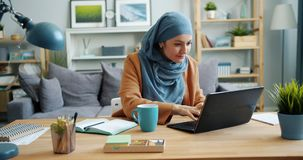 Independent girl in hijab freelancer working with laptop in apartment. Typing sitting at desk alone. Modern people, communication and technology concept stock video footage