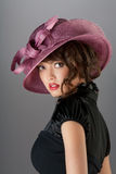 Independent look. A portrait of a sexy hot brunette with curly hair wearing a beautiful stylish hat Stock Image
