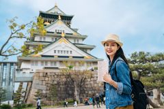 Independent travel in japan lifestyle concept. woman traveler holding guidebook visiting osaka castle alone carrying backpack and. Slr camera. young girl face royalty free stock photos