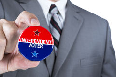 Independent voter. A man in a business suit holds out a political independent voter pin during elections Stock Images
