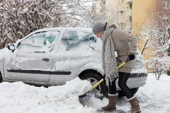 Independent woman shoveling snow in winter. Royalty Free Stock Image