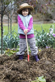 Independent young kid enjoying posing on top of manure pile. Kid gardening concept - thrilled child posing with a shovel on top of a pile of manure in home Stock Photo