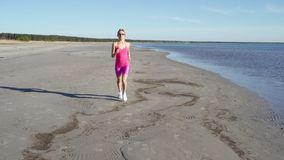 Independent young woman athlete running on beach exercising female runner sprinting training in sunny seaside background stock footage