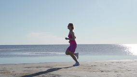 Independent young woman athlete running on beach exercising female runner sprinting training in sunny seaside background stock video