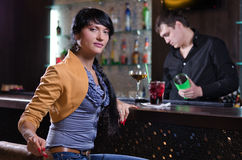 Independent young woman relaxing alone at the bar Stock Image