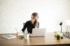 Attractive female worker in an office Stock Photos
