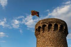 Independentistvlag die bovenop middeleeuwse torenwolk golven stock fotografie