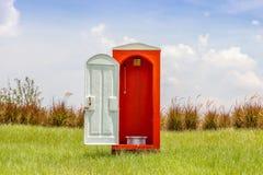 Independiente de retrete rojo con contraste abierto de la puerta blanca con gree imágenes de archivo libres de regalías
