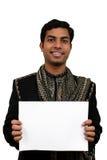 Inder in der traditionellen Kleidung, die in der Hand einen weißen Vorstand (2) anhält Stockfotografie