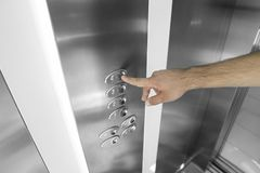 Index appuyant sur le quatrième bouton de plancher dans l'ascenseur photo libre de droits