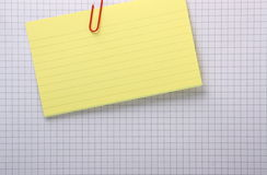 Index Card and Graph Paper Background. A yellow index card clipped with a paperclip to a grey lined sheet of graph paper with copy space Stock Image