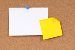 Office index card with post it style yellow sticky note pinned to cork board, copy space. Office index card and sticky note pinned to a cork bulletin board stock photo