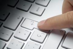 Index finger pressing enter key stock photo