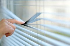 Index finger when pressing the transverse strip blinds. For a better view outside the window Royalty Free Stock Photography