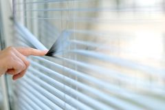 Index finger when pressing the transverse strip blinds. For a better view outside the window Royalty Free Stock Photos
