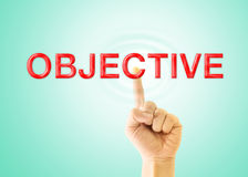 Index finger touch to the word. OBJECTIVE  on light green background Stock Photos
