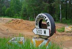 Index & x22; gummihjulet efter 500 meters& x22; på bakgrunden av den brutna vägen Royaltyfri Bild
