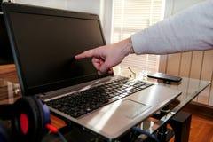Index masculin de main environ pour taper une maison de te d'écran d'ordinateur portable photo stock