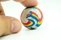 Index or pointing finger touching colorful rubber marble ball is Royalty Free Stock Images
