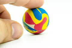 Index or pointing finger touching colorful rubber marble ball is Royalty Free Stock Photography