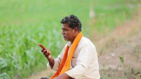 Indiański średniorolny używa telefon komórkowy przy kukurydzanym polem zbiory