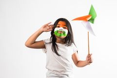Indiańska mała dziewczyna i tricolour twarzy mienia wiatraczek robić up szafran, colour papier, szczęśliwa niezależność lub repu, Obraz Stock