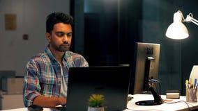 Indiański mężczyzna z laptopem pracuje przy nocy biurem zbiory wideo
