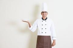 Indiański męski szef kuchni trzyma talerza w mundurze Fotografia Royalty Free