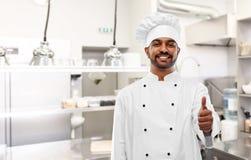 Indiański szef kuchni pokazuje aprobaty przy kuchnią fotografia stock