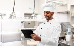 Indiański szef kuchni z pastylka komputerem osobistym przy restauracyjną kuchnią obrazy royalty free