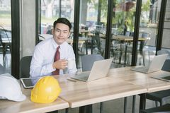 Civil Engineer working project on site with laptop and white hard hat. stock image