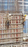 India contruction site workers disregard safety. Editorial vertical portrait of men at work disregard health and safety on a 18 floor construction site wearing Royalty Free Stock Image