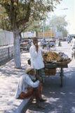 1977 India Een oude mensenzitting op een voetpad, die zijn chillum-pijp roken Stock Foto