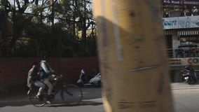 INDIA - FEBRUARY 2018: People walking, riding bicycle and cars running on the street. INDIA - FEBRUARY 2018: A view along streets of during the day showing stock video