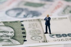 India financial and economy, new emerging market high growth country concept, closed up of miniature businessman foreigner. Standing on Indian rupee banknotes stock images