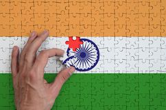India flag is depicted on a puzzle, which the man`s hand completes to fold.  vector illustration
