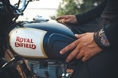 India, Goa -April 6, 2017: Man`s hand with a watch on the fuel tank of the Royal Enfield motorcycle Stock Photo