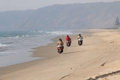 India, GOA, Styczeń 22, 2018 Dziewczyna i facet jedziemy hulajnogę wzdłuż seashore Hulajnoga na plaży fotografia stock