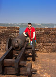 India. Goa. The teenager near a gun on a wall of an ancient fort Royalty Free Stock Photo