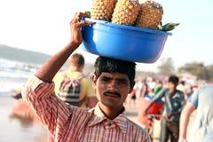 India. Goa. Um homem novo vende abacaxis. Fotos de Stock Royalty Free
