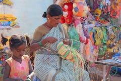 India, Hampi, 02 Februari 2018 Een vrouw is bezig geweest met handwerk, weeft manden plastiek De verkoopster in de markt handel stock afbeelding
